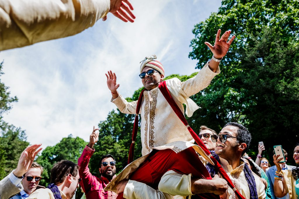 indian groom on friends shoulders