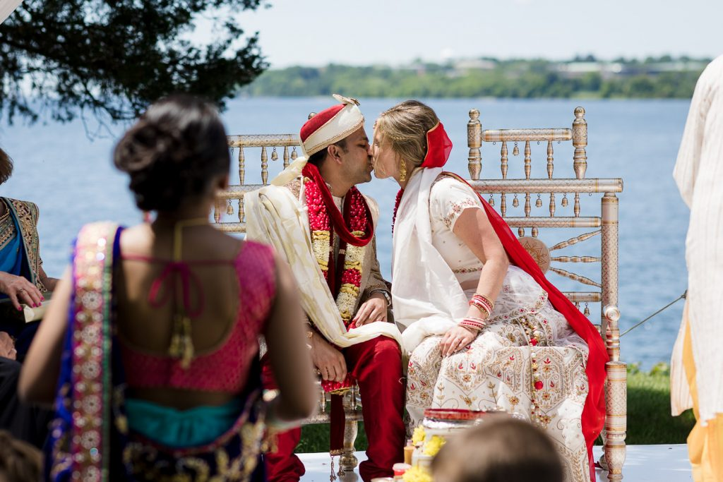 bride and groom kiss during indian wedding ceremony