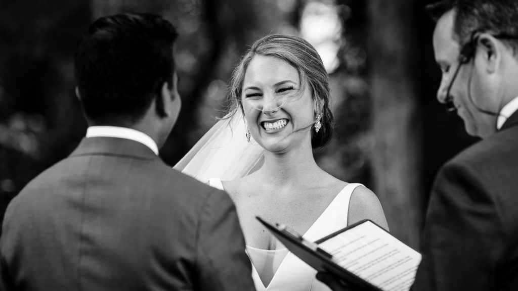 bride smiles big during wedding ceremony