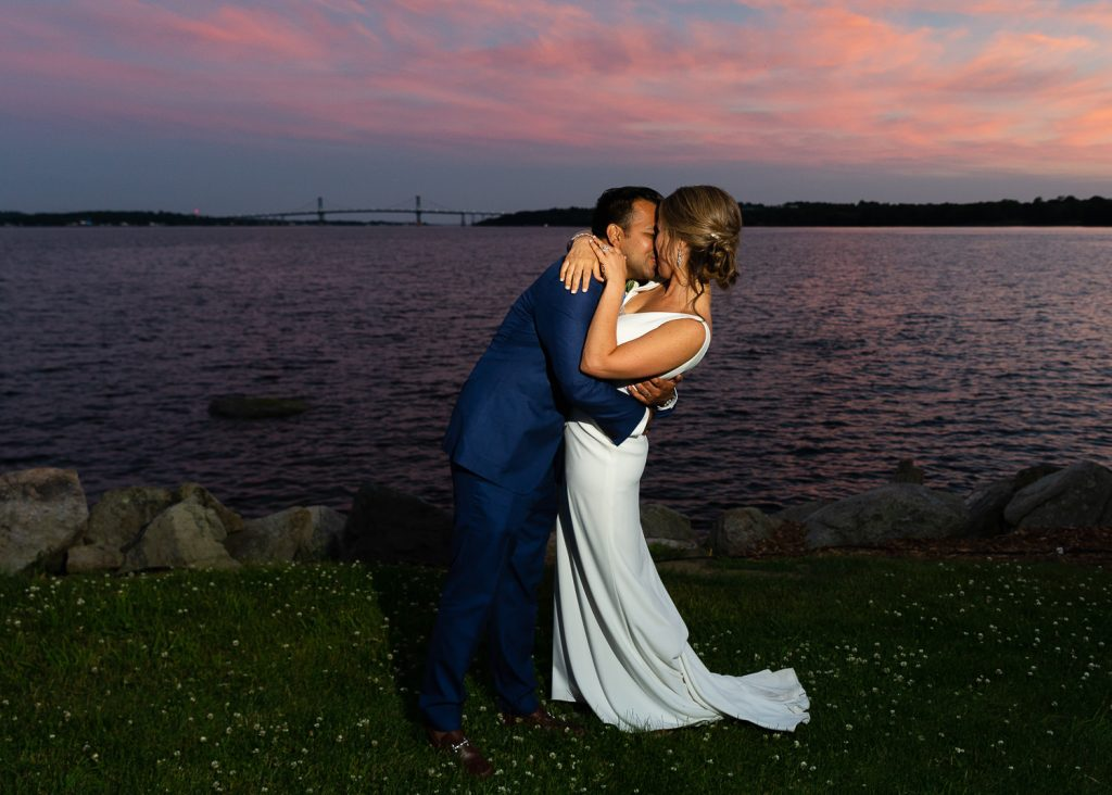 groom dips bride under sunset bridge