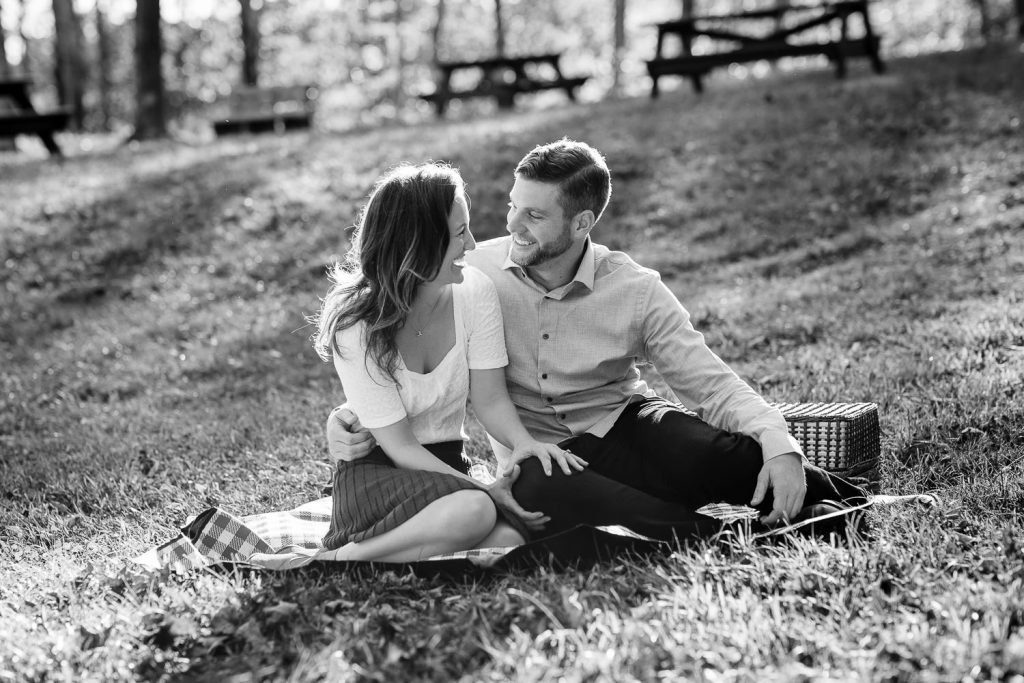 A man and woman share an intimate moment on a picnic blanket in a central ma park during their engagement photography session
