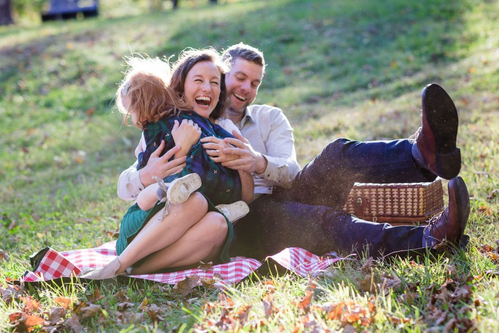 A little girl runs and jumps into her parents arms as they sit on a picnic blanket