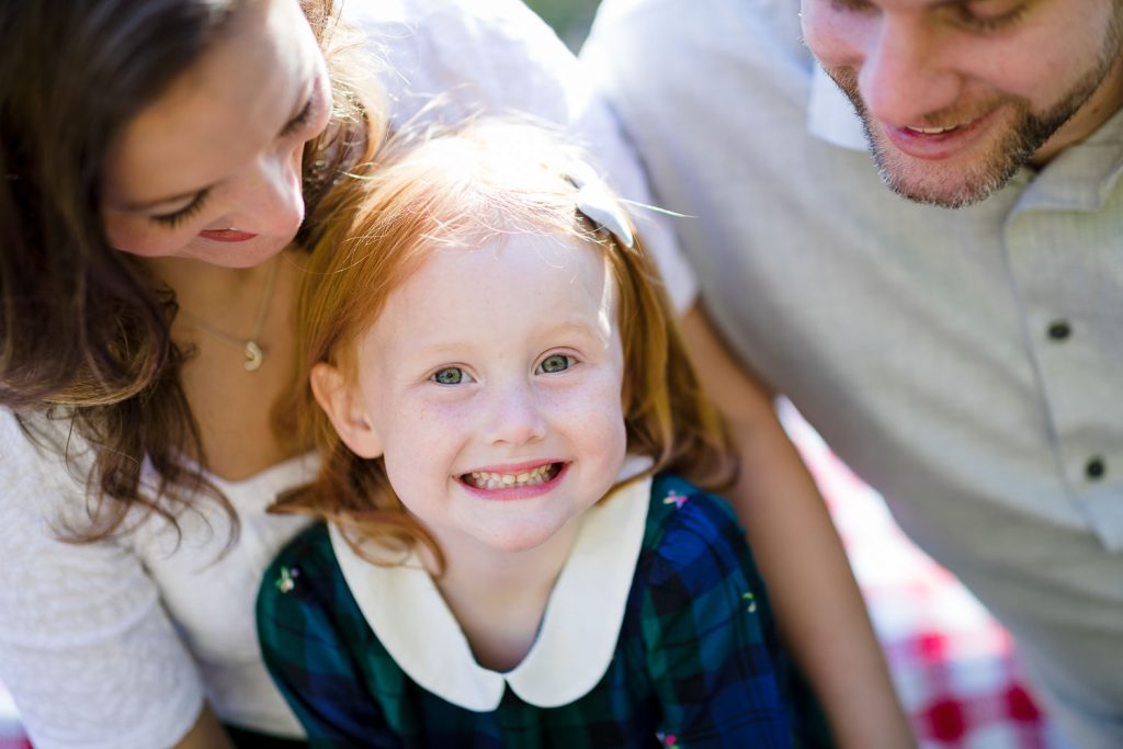 A little girl smiles as her parents look lovingly at her