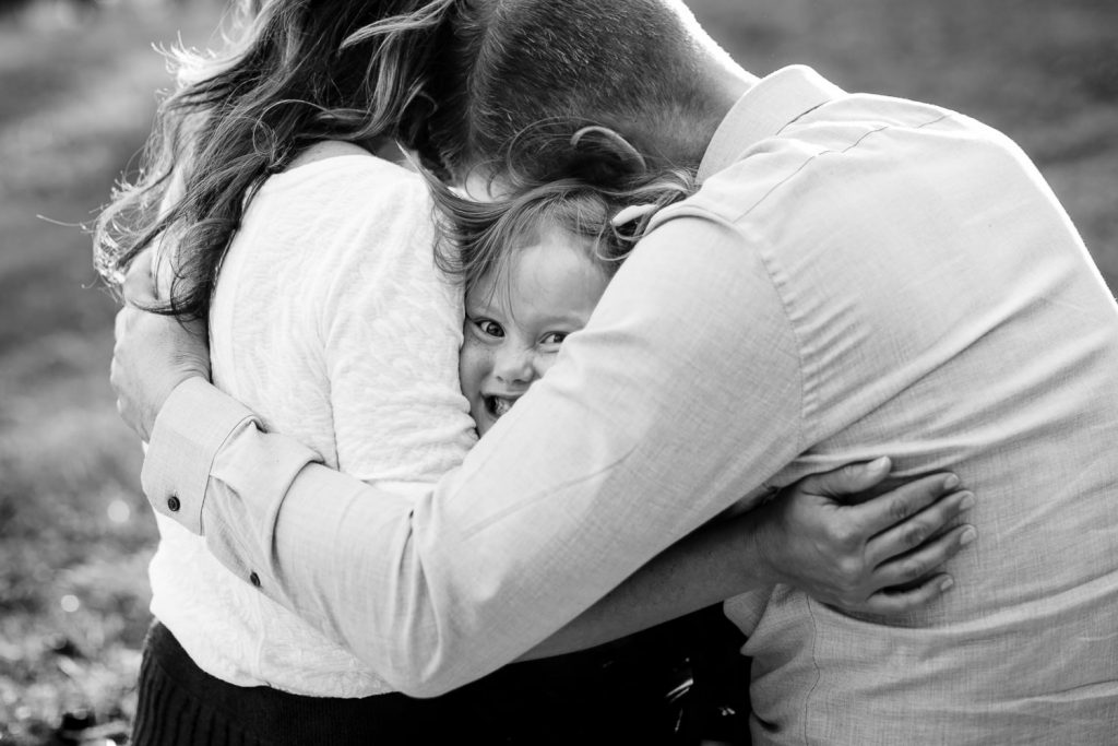 A little girl smooshes her face out from between her parents hug