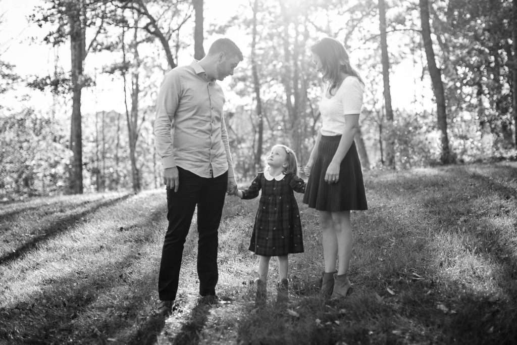 A little girl holds hands with her mom and dad during a central ma engagement session