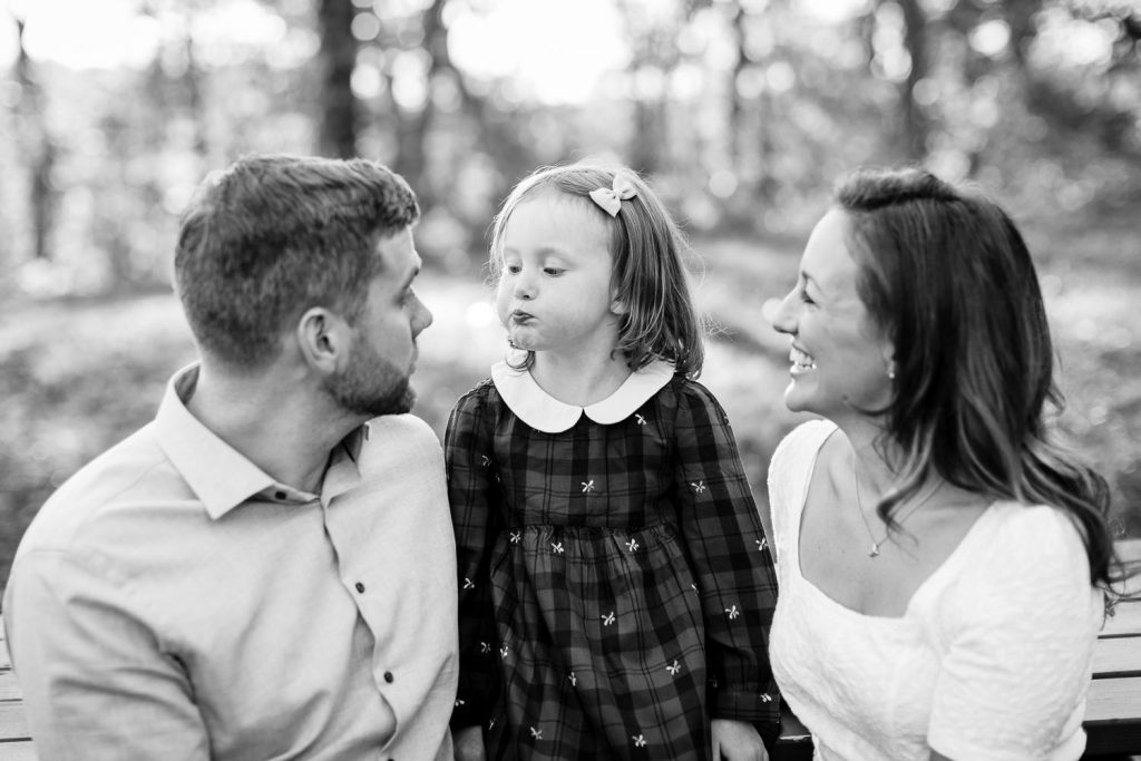 A little girl sits between her mom and dad and makes a funny face