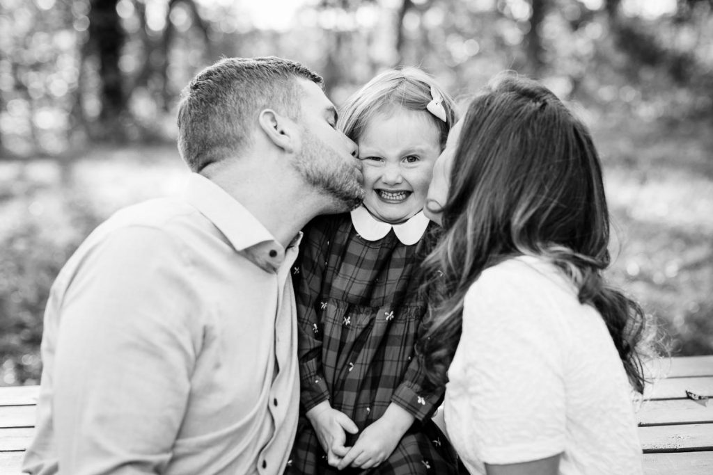 A mom and dad kiss a little girls cheeks