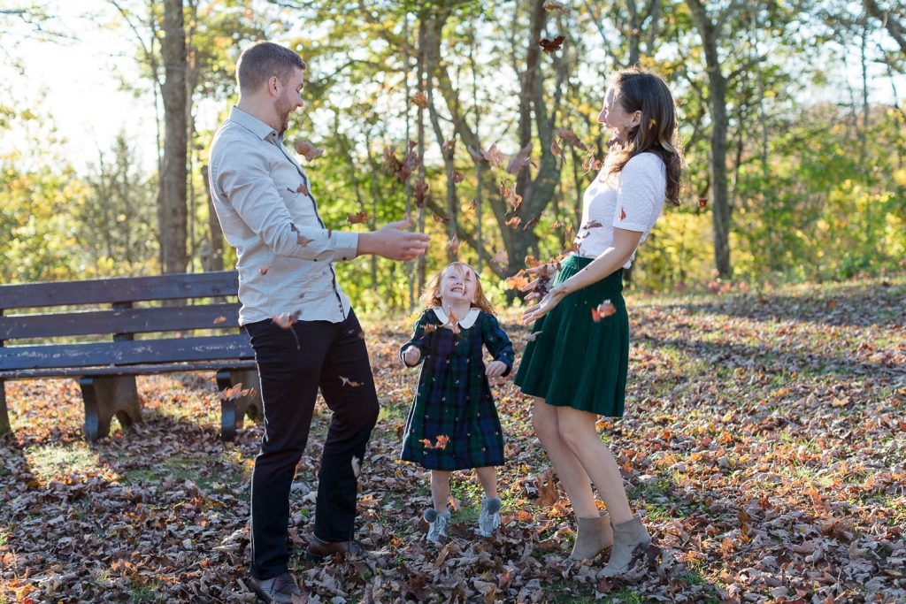 A family throws fall leaves in the air during a photo session at moore state park in central ma