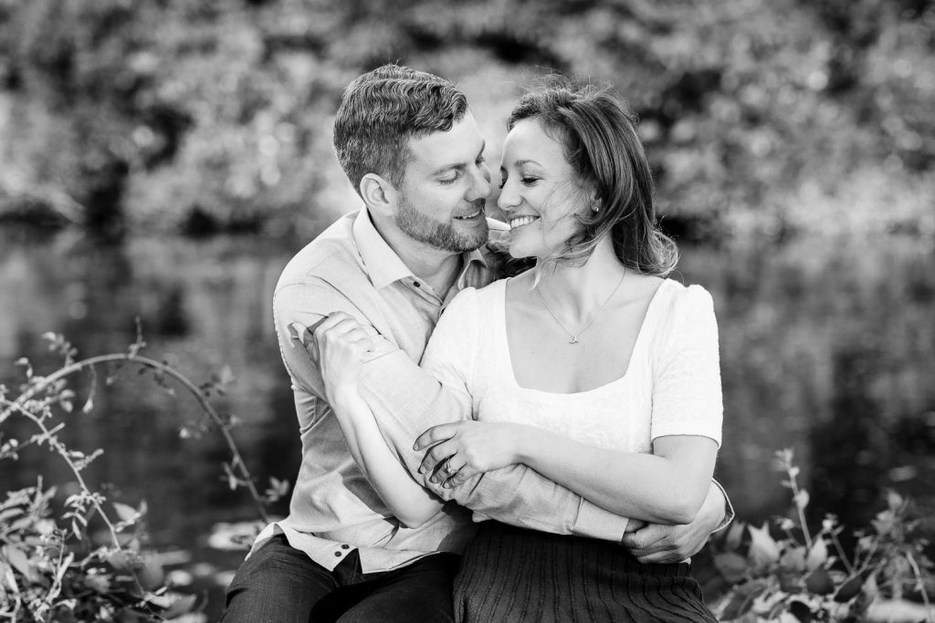 A man and woman snuggle by a pond during their engagement photography session in central ma