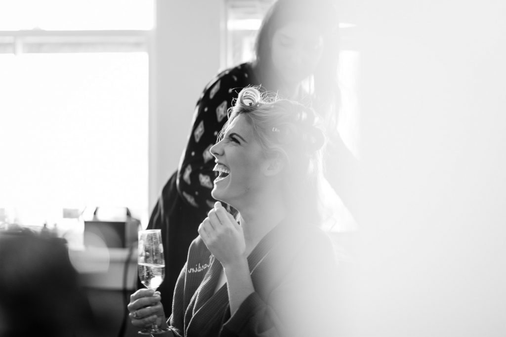 bride laughing during hair and makeup