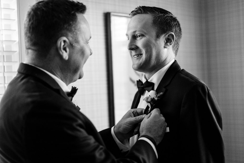 The father of the groom adjusting his son's boutonniere on his wedding day