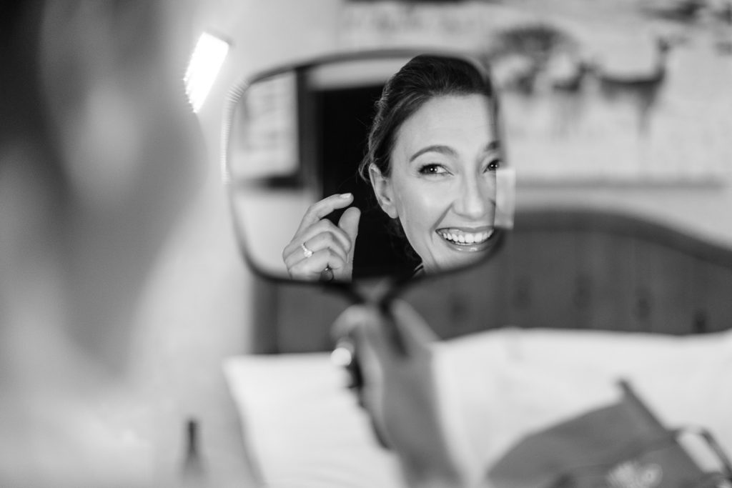 A bride laughs as she looks in the mirror on her wedding day