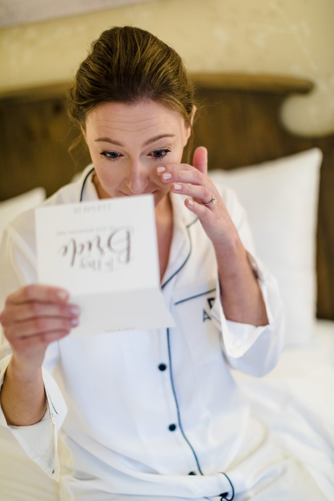 A bride in pjs dabs a tear from her eye as she reads a letter from her groom