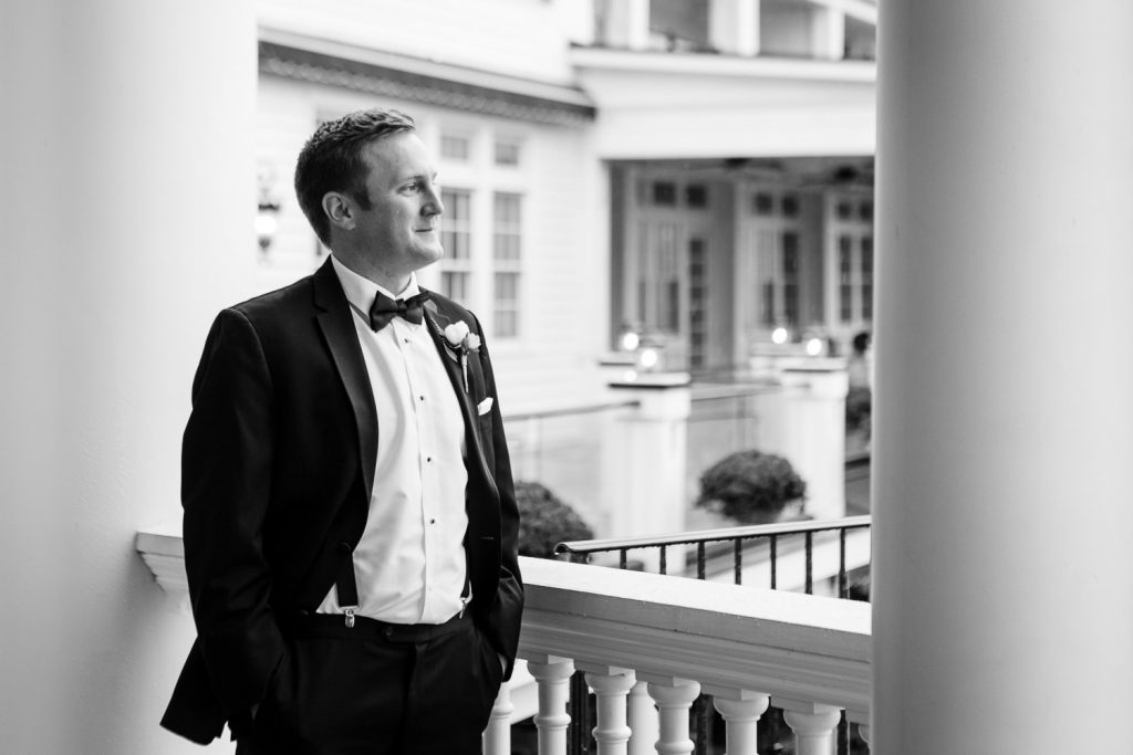 A groom in a black tuxedo looks out from under the portico at the Sagamore Resort on lake george