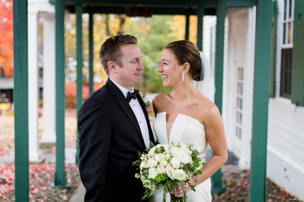 A bride and groom look in each others eyes with fall foliage in the background at their lake george wedding