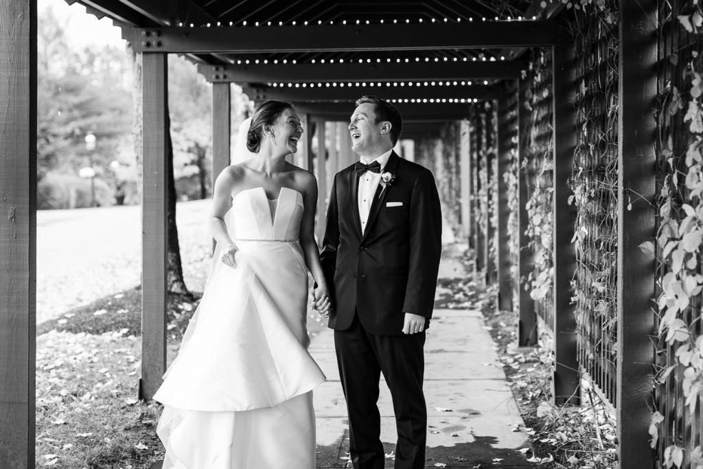 A bride and groom laugh as they walk down a covered walkway at the sagamore resort on lake goerge