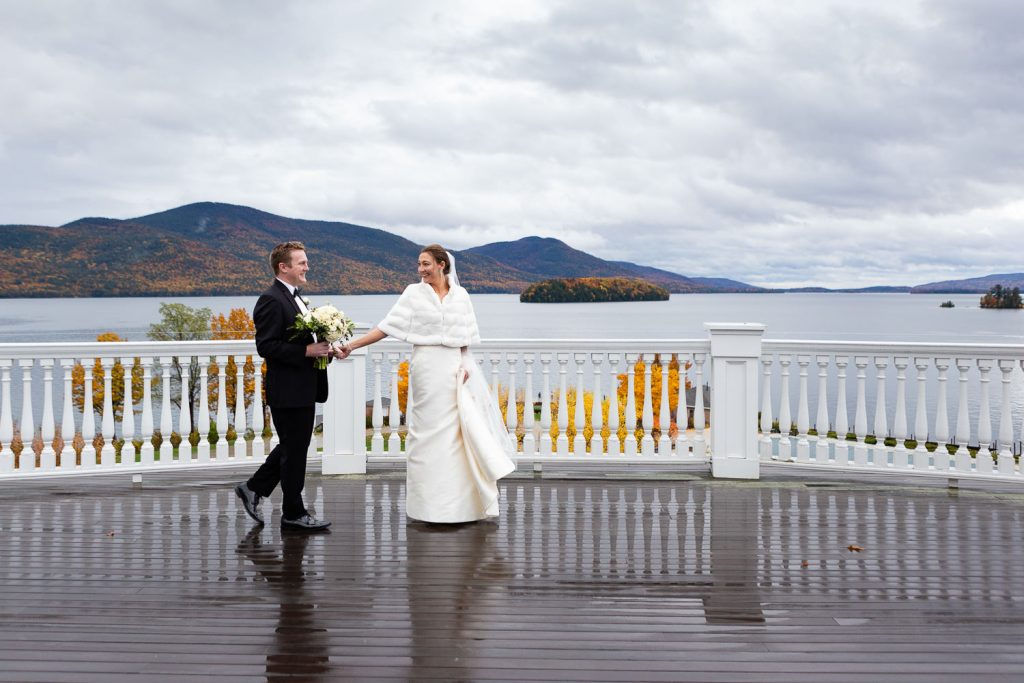 A bride pulls her groom across the balcony of the sagamore with lake george in the background at their wedding