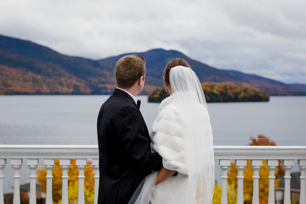 A bride and grooms backs as they look out over the fall foliage of lake george at their november wedding at the sagamore resort
