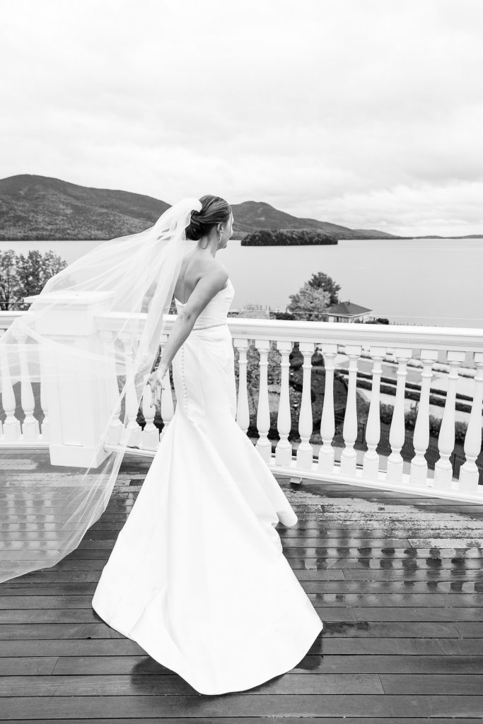 A bride holds her veil as it flows in the wind at her sagamore lake george wedding