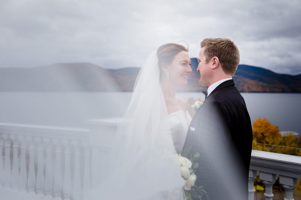 A bride and groom go in for a kiss as her cathedral veil flows in the wind at their lake george wedding