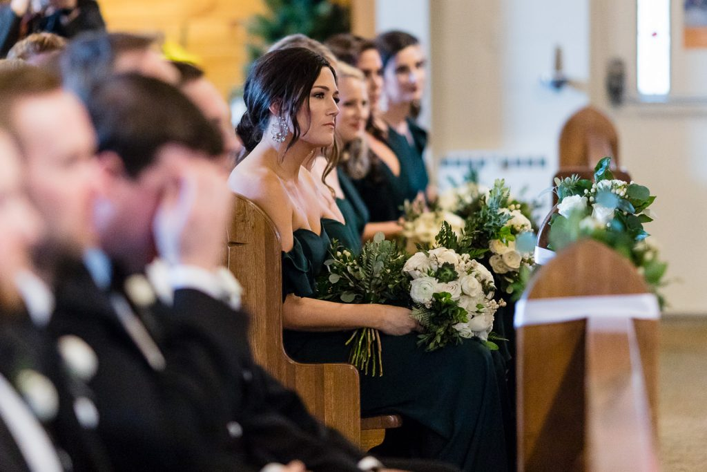 A row of bridesmaids in a pew look on as a wedding ceremony happens