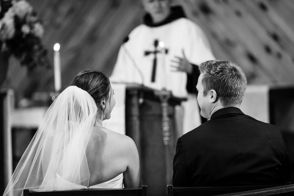 A bride and grooms backs as they look up at the priest that is marrying them in bolton landing ny