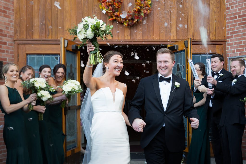 A bride and groom run out of a church amidst confetti at their lake george wedding
