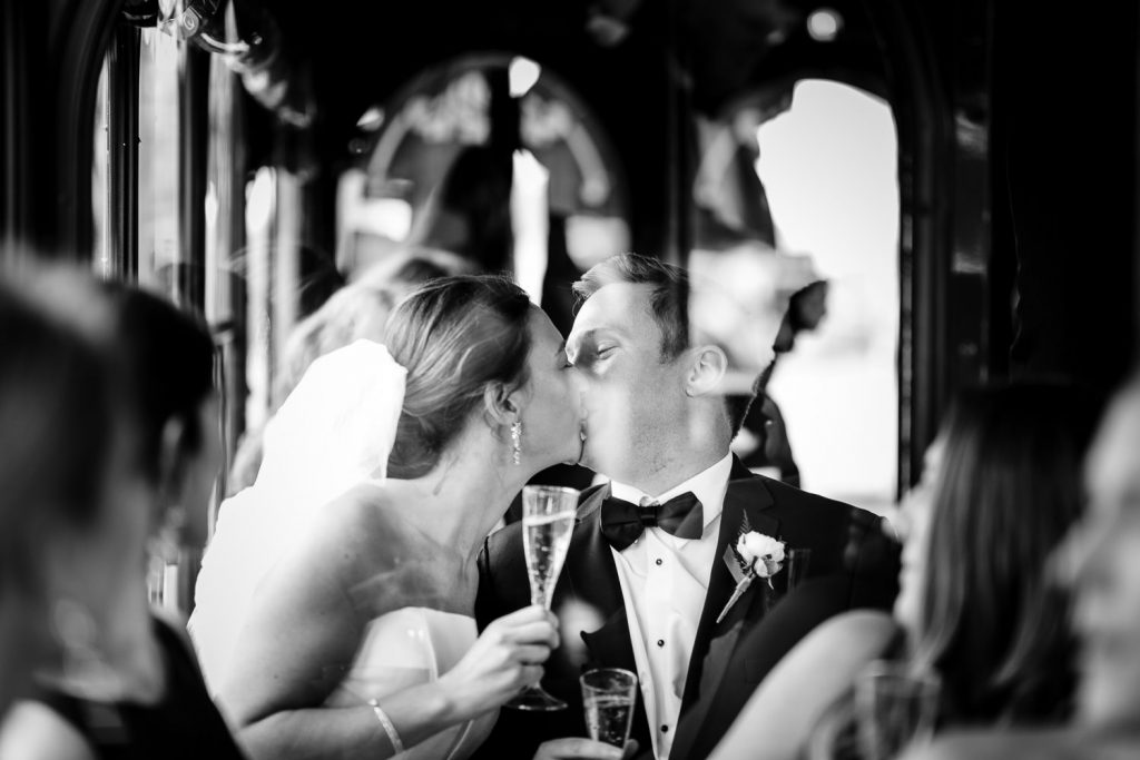 A bride and groom kiss behind the glass window of their wedding trolley on lake george