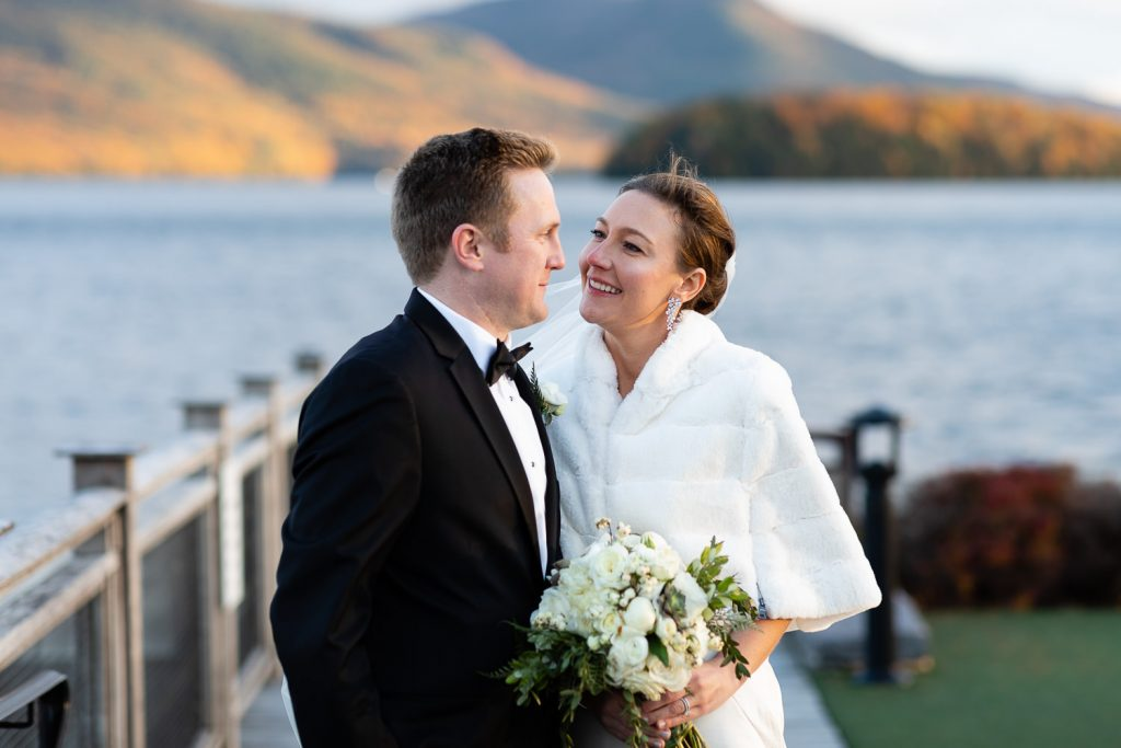 A bride and groom look into each others eyes at sunset on the docks of lake george