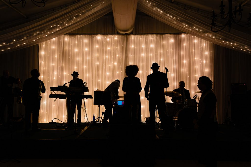 The new york players band in silhouette on the stage at a sagamore lake george wedding