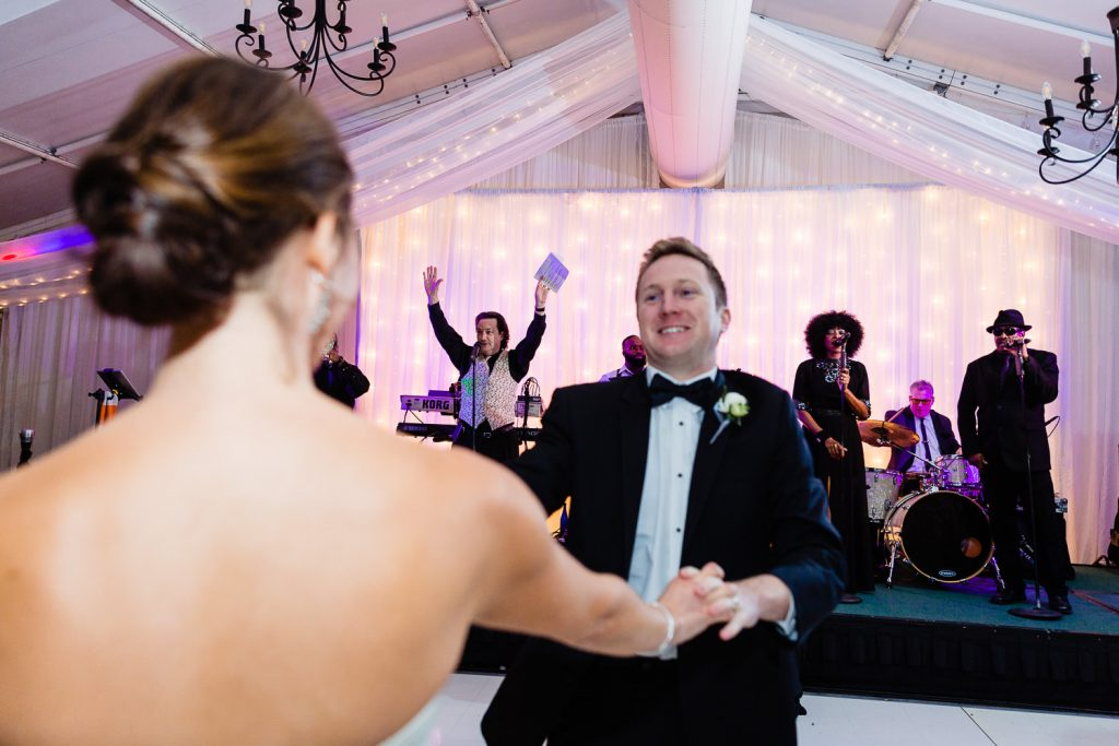 A bride and groom swing each other around the dance floor as the wedding band plays in the background