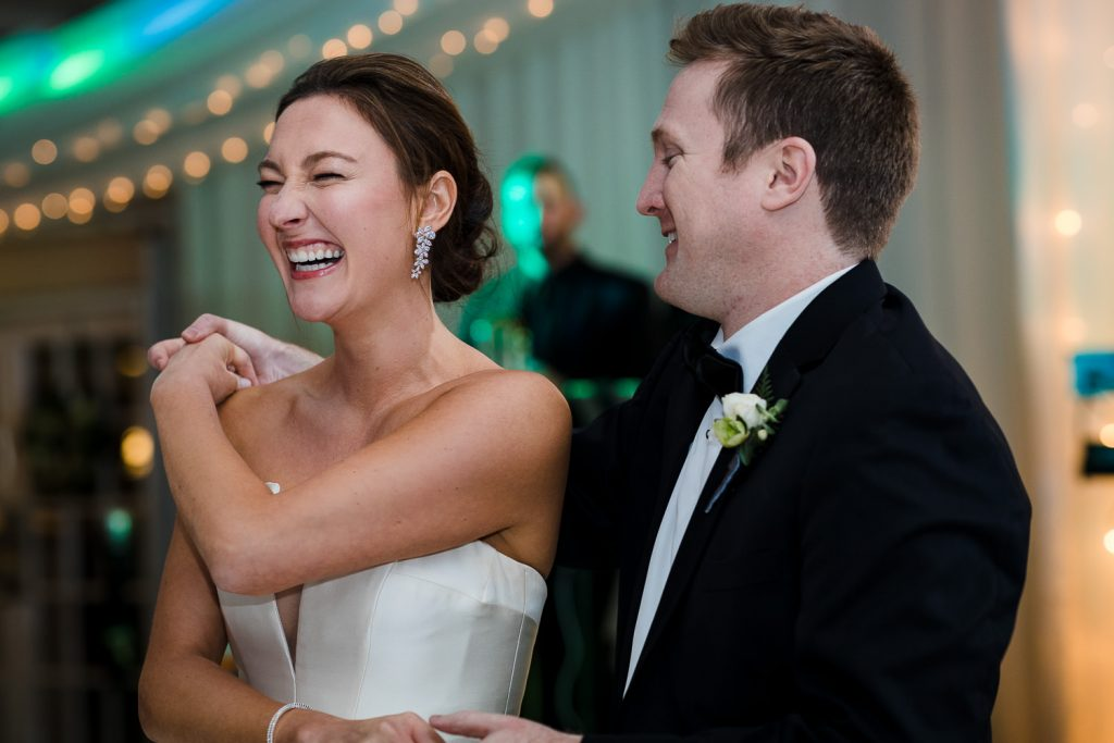 The bride laughs as her groom spins her around during their first dance
