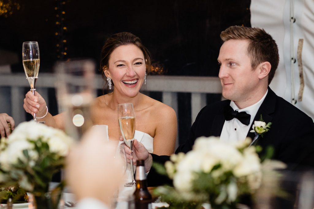 A bride and groom toast amidst champagne glasses at their wedding reception
