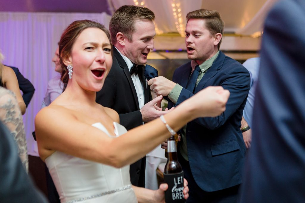 A bride and groom extend imaginary microphones during their wedding reception