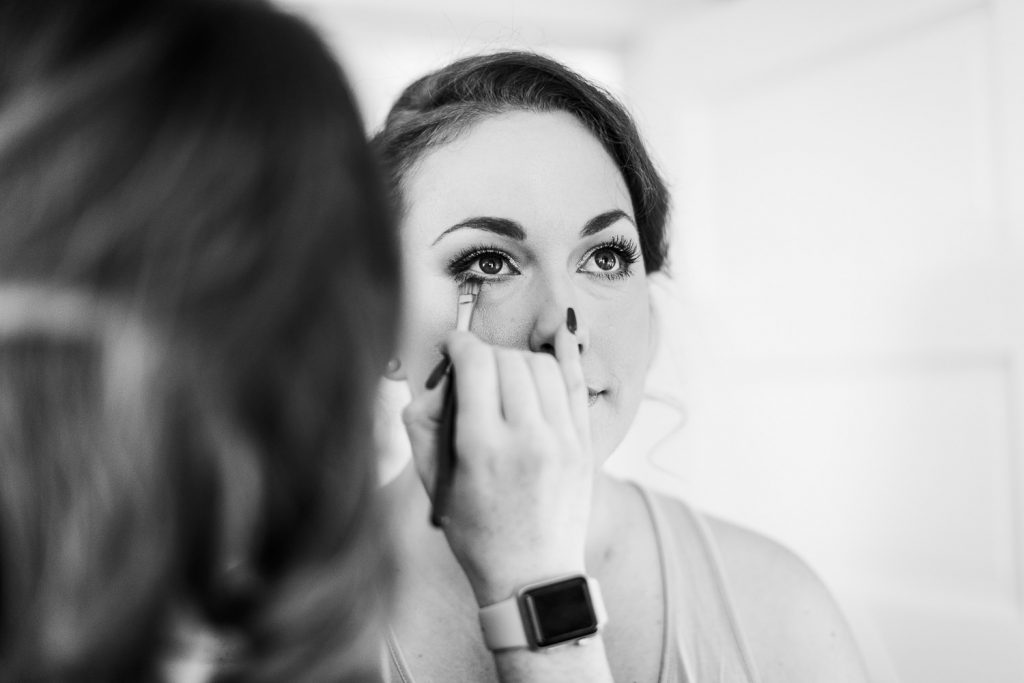 A bride gets her eye makeup done for her wedding