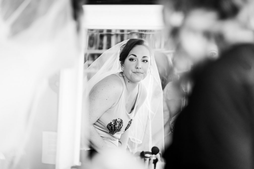 A bride looks in the mirror to see her hairdo and veil