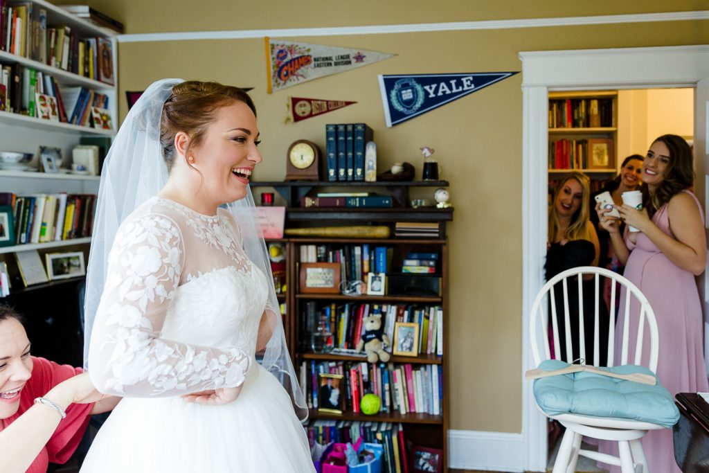 A bride is overcome with happiness as she looks at herself in the mirror in her wedding gown