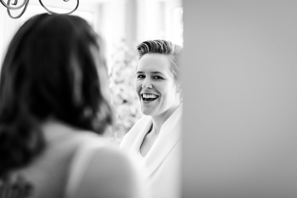 A bride laughing as she gets ready for her wedding