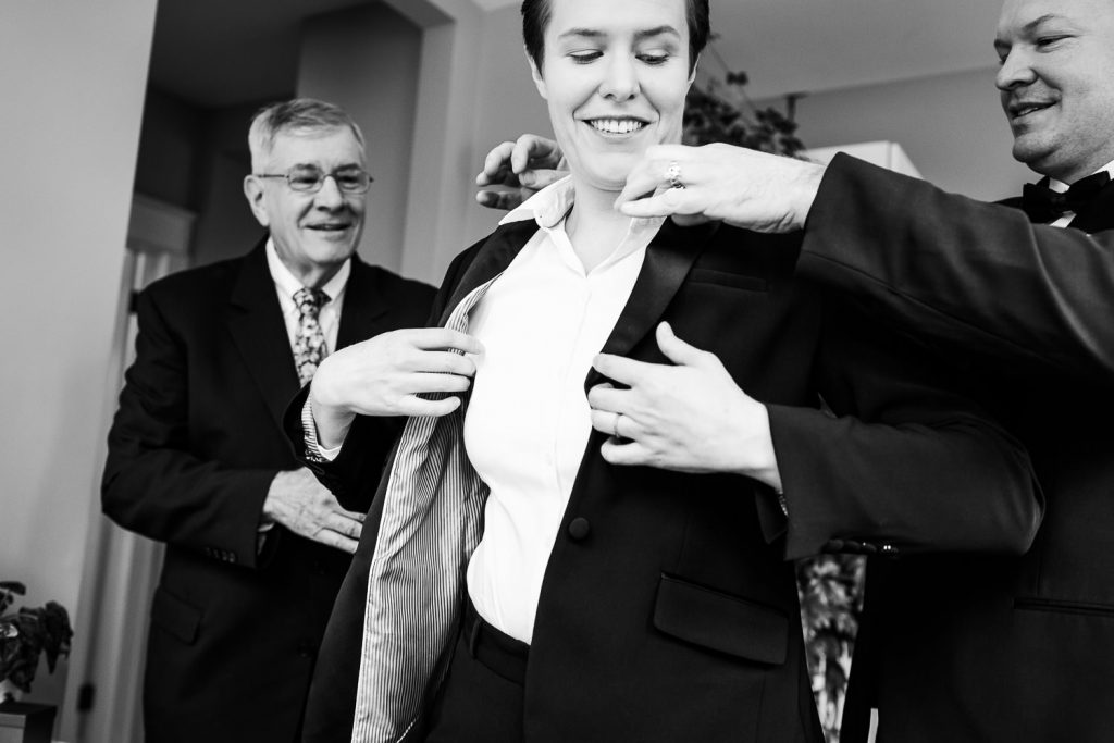 A bride puts on her suit jacket with help from her father and brother