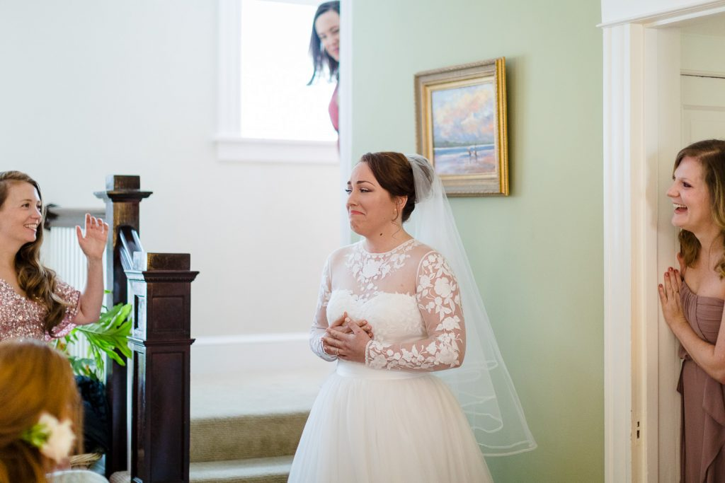 A bride is emotional as she comes down the stairs revealing her wedding dress to her friends
