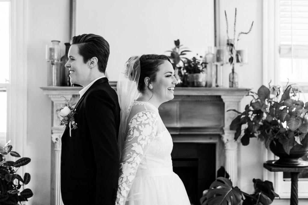Two brides stand back to back in the living room of their home waiting to do their wedding first look