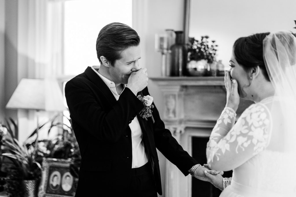 Two brides hold their hands over their mouths in disbelief after seeing each other for the first time at their westport ct wedding