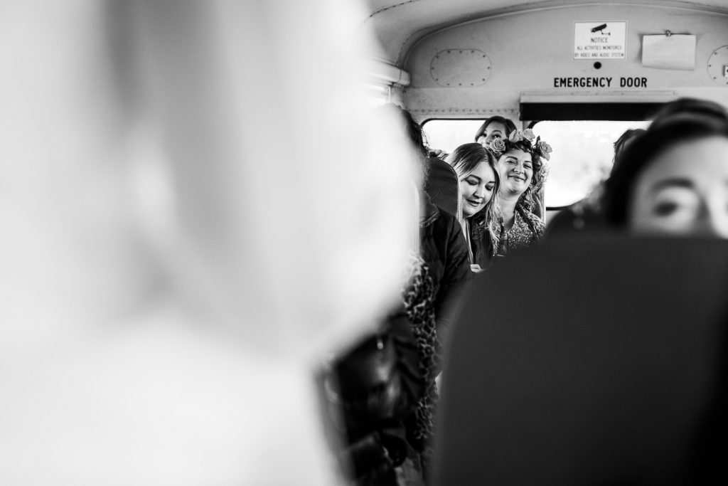 Friends on a school bus react to seeing the bride get on the bus