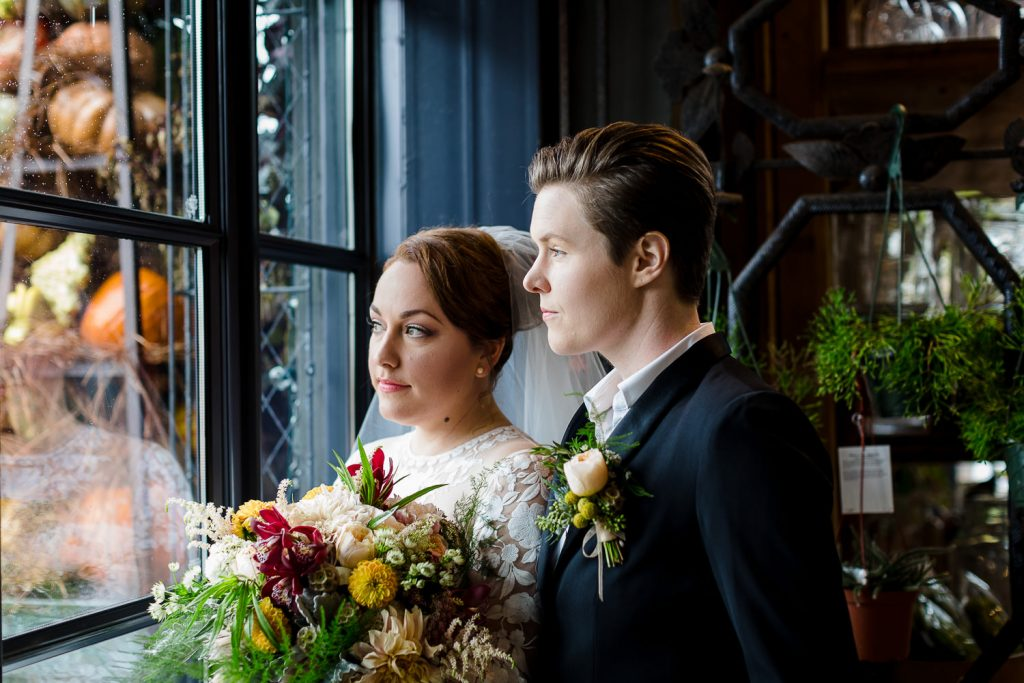 Two brides look out a window during the portrait session at their westport ct wedding