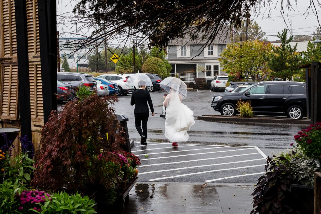 Two brides walk through a parking lot under clear umbrellas