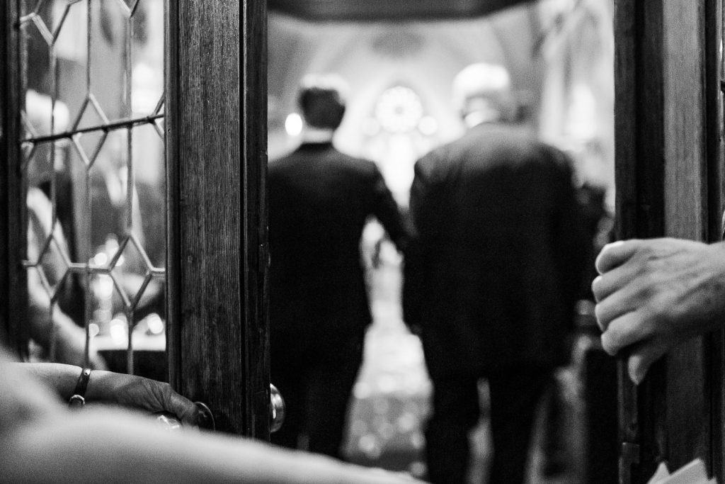 Hands opening the door to a churh to reveal a father walking his daughter down the aisle