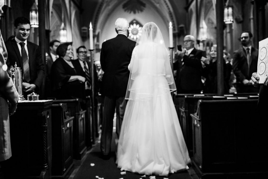 A father walks his daughter down the aisle at her church wedding