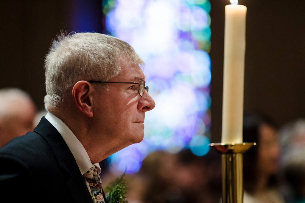 A father watches his daughter get married in front of a stained glass window at the church