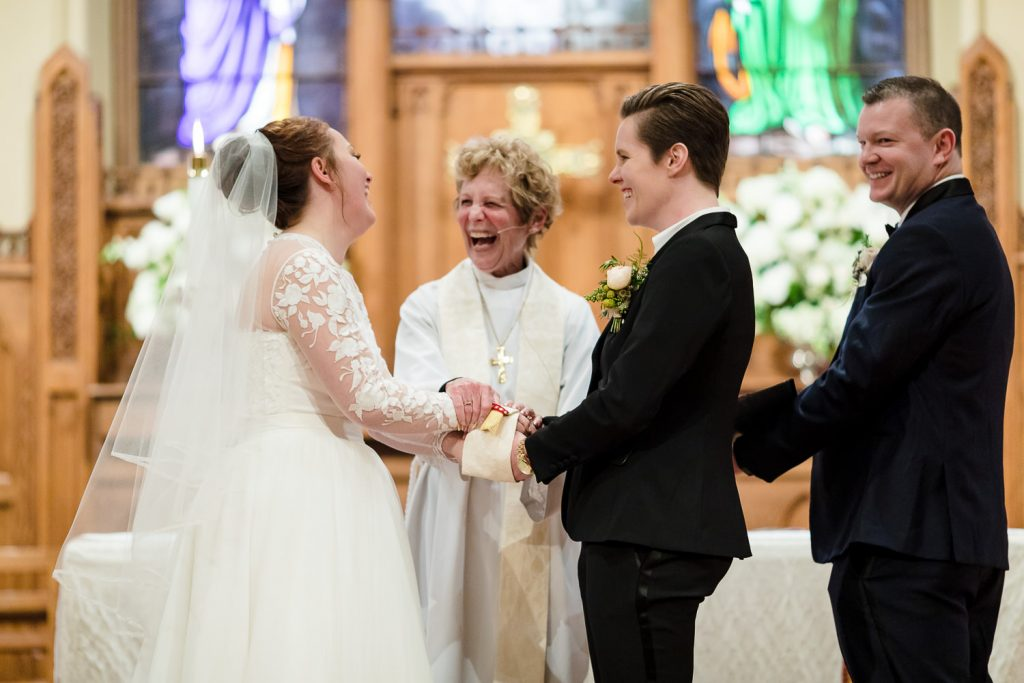 Two brides laugh along with the officiant at their wedding ceremony