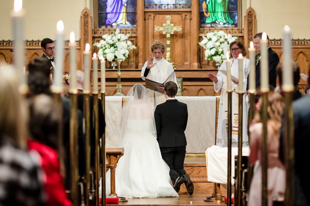 Two brides kneel at the alter of their lgbt episcopal wedding ceremony